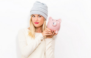 Young woman with a piggy bank on a white background