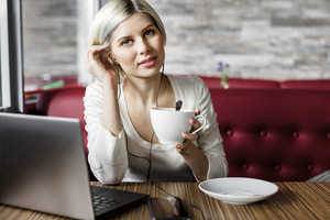 Young Woman With Coffee Cup And Laptop In Cafe