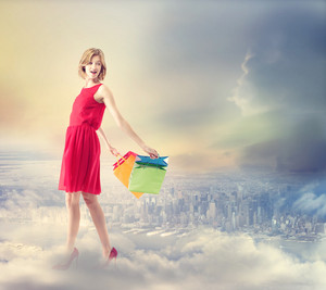 Young woman with colorful shopping bags above a city