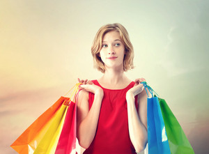 Young woman with colorful shopping bags wearing a red dress