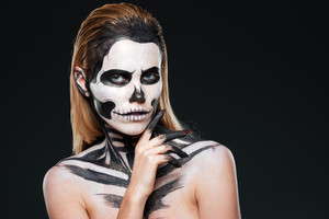 Young woman with gothic skeleton makeup over black background