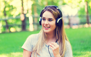 Young woman with headphones outside on a summer day
