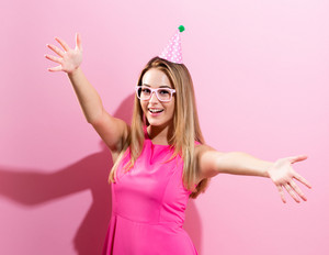 Young woman with party hat on a pink background
