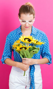 Young woman with sunflowers on pink background