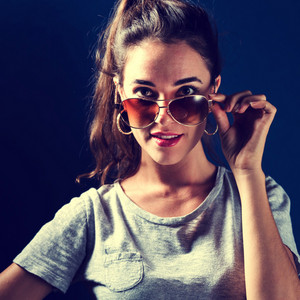 Young woman with sunglasses on a dark blue background