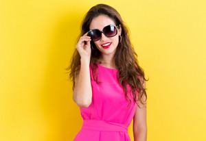 Young woman with sunglasses on a yellow background