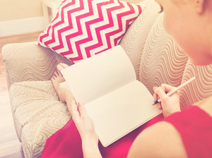 Young woman writing in her notebook on at home on her couch
