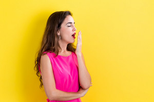 young woman yawning on a yellow background