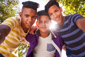 Youth culture, young people, group of male friends, multi-ethnic teens outdoors, teenagers together in park. Portrait of happy boys smiling, kids looking at camera. Slow motion