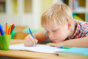 Youthful learner making notes or drawing with pen at lesson