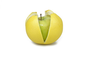 Green Apple In A Grapfruit Peel On White Background