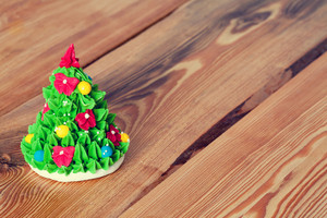 Green marzipan sweet christmas tree on wooden background