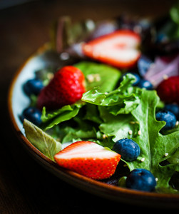 Green Salad With Berries On Wooden Background