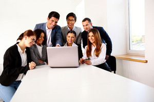 Group of a happy businesspeople working on the laptop at meeting