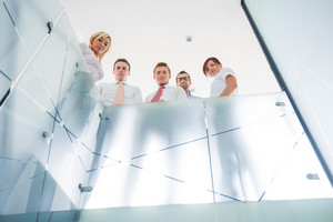 Group of business people posing behind a glass railing