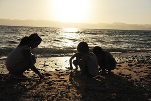 Group of children playing in sand before sunset