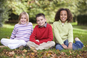 Group of children sitting in autumn garden