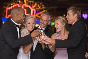Group of friends celebrating with champagne in casino