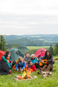 Group of friends sitting beside tents,campfire girl playing guitar