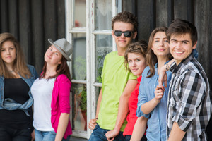 Group of happy young people in front of old wooden house