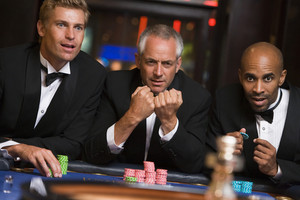 Group of male friends gambling at roulette table in casino
