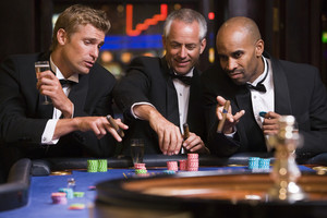 Group of men gambling at roulette table in casino