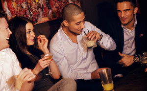 Group of men having fun together with their pretty female friend at the bar