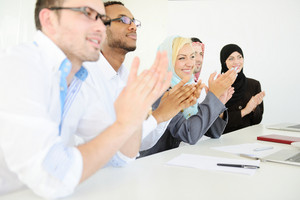 Group of multi ethnic business people applauding during presentation