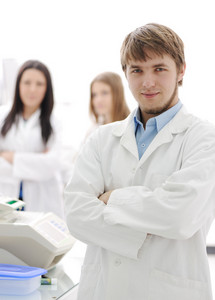 Group of scientists standing  at the laboratory, young doctor with folded arms