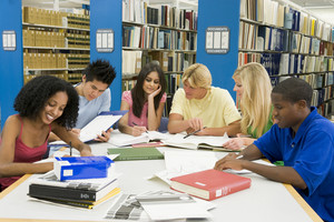 Group of six students working around table in library