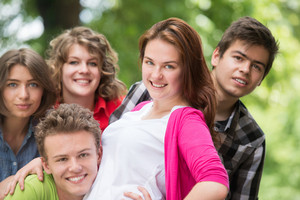 Group of smiling happy young people in woods