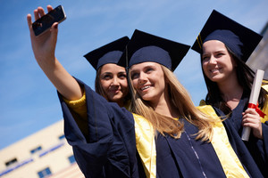 Group of students in graduates taking selfie