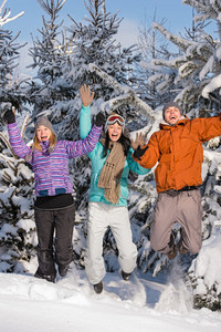 Group of teenagers jumping together in wintertime snowy forest
