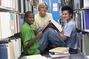 Group of three male students sitting on floor of library surrounded by books