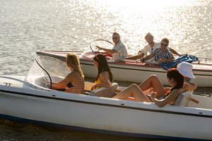 Group of women and men navigating motorboats summer lake