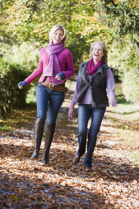 Grown up mother and daughter on walk through autumn woods