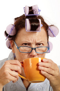 Grumpy Middle-aged Woman With Hair Rollers Drinking Coffee
