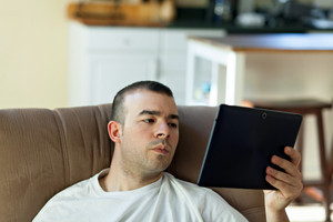 Guy holding and reading something on his portable tablet computer.