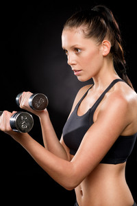 Half length of a young woman lifting dumbbells in sportswear