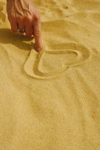 Hand Drawing Heart In Sand On The Beach