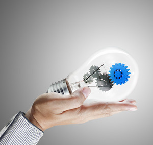 Hand Holds Blue Gear In Light Bulb
