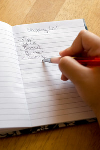 Hand writing out a grocery shopping list with a pen and pad.