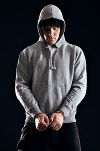 Handcuffed offender wearing a hooded sweatshirt