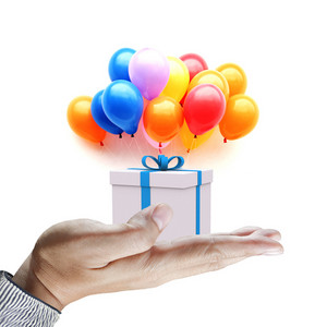 Hands Holding Gift In Package With Blue Ribbon And Colorful Balloons