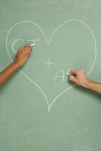Hands writing on chalkboard
