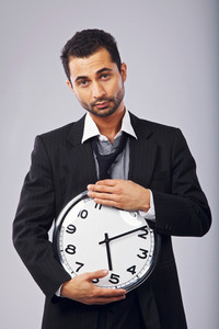 Handsome and young office worker holding a wall clock