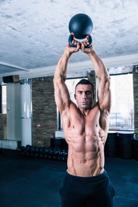Handsome bodybuilder man workout with kettle ball in crossfit gym