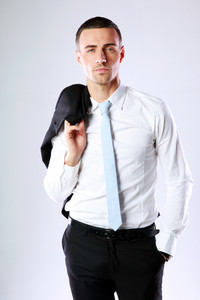 Handsome business man holding jacket on shoulder on gray background