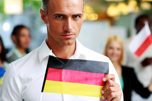 Handsome businessman holding flag of Germany in front of colleagues