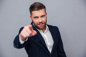 Handsome businessman pointing finger at camera